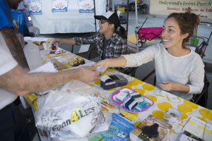 Kate Miller (right) and Elizabeth Bowman (left) assist shoppers redeeming CalFresh benefits at the Hollywood Farmers Market. Shoppers visit the Farmers Market manager's table where they can swipe their EBT card in exchange for paper vouchers to use throughout the market.